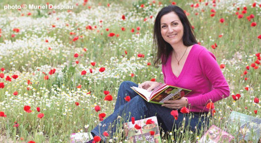 Valérie Cupillard dans l'herbe avec ses livres de recettes