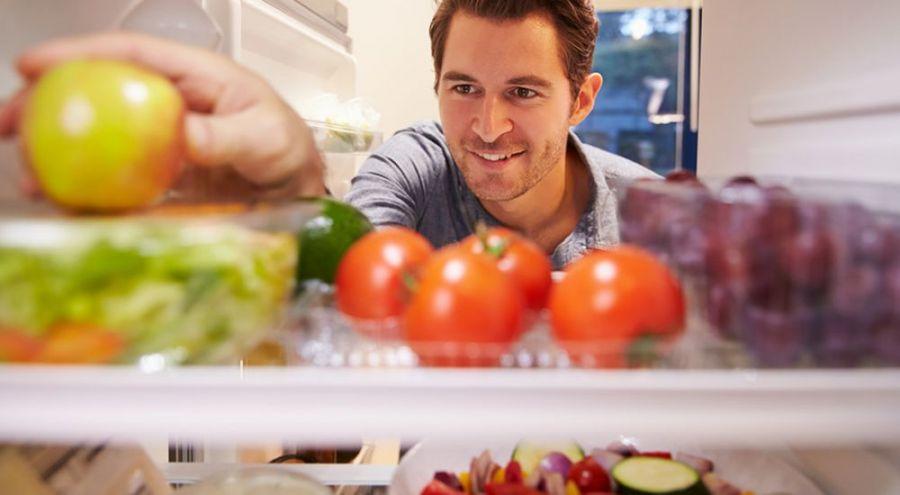 Homme prenant une pomme dans un frigo