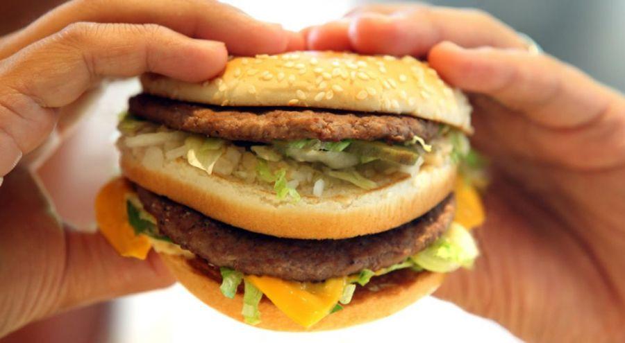 Homme tenant un hamburger dans ses mains