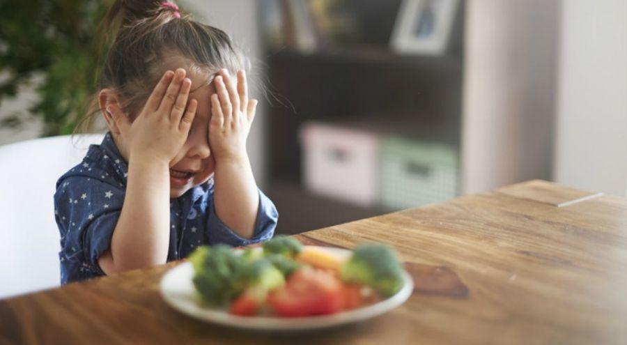Petite fille qui refuse de manger des légumes