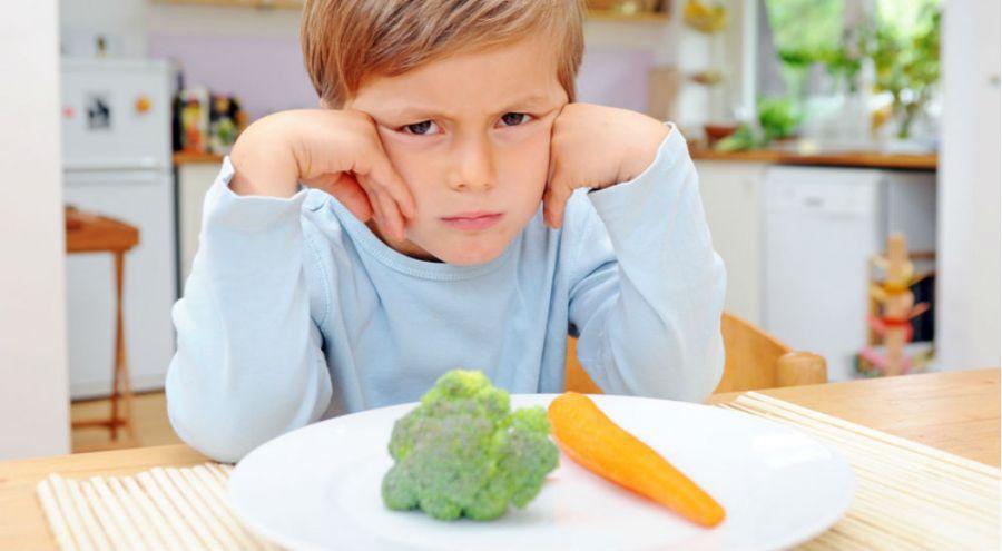 Enfant qui boude devant une assiette de légume