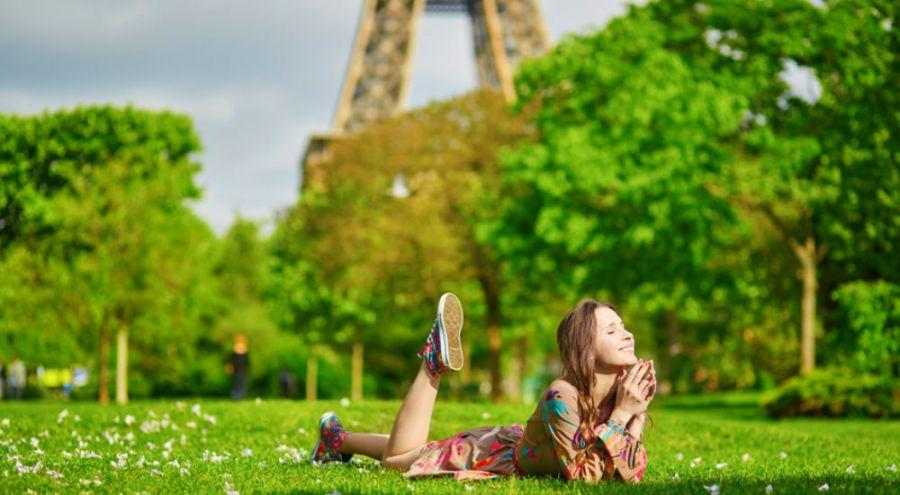 Femme allongée dans l'herbe au pied de la Tour Eiffel