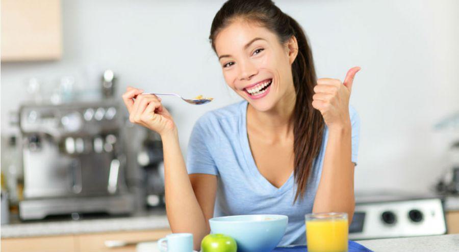 Femme souriante prenant son petit déjeuner