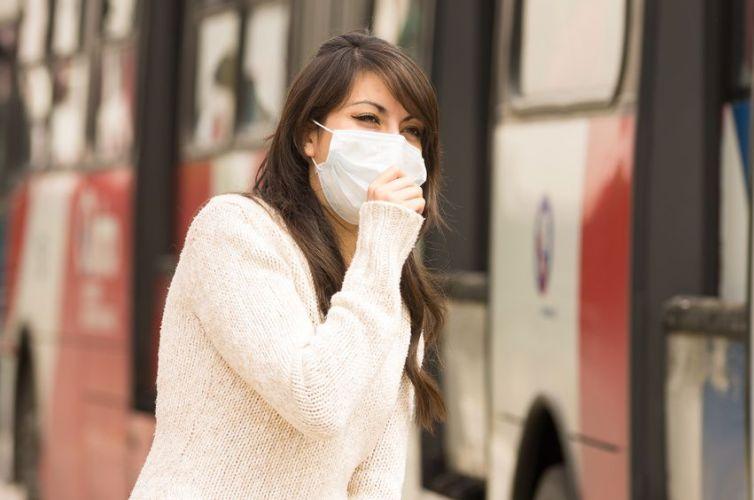 Une femme avec un masque se promène près d'un bus en ville