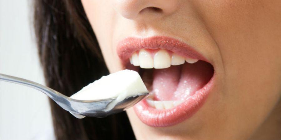 femme portant une cuillère de yaourt à sa bouche