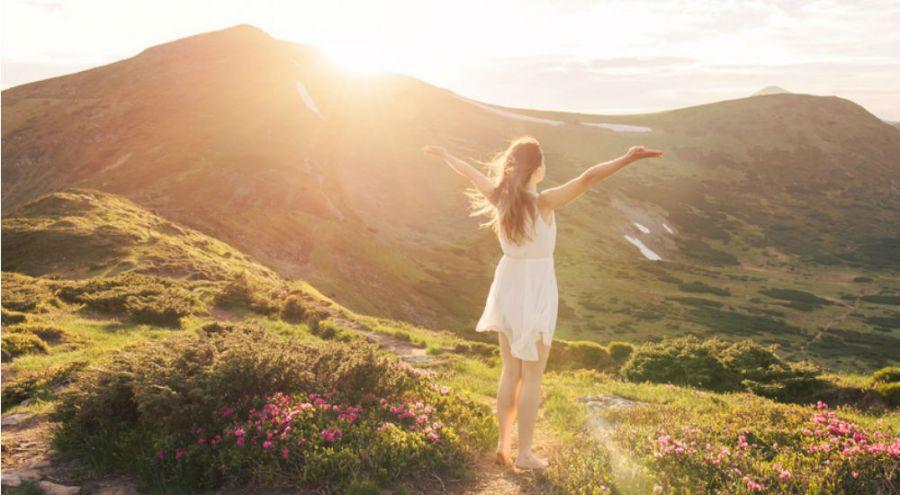 femme en robe blanche dans la nature face à un lever de soleil