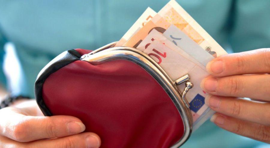 La main d'une femme sort un billet de banque du porte monnaie.