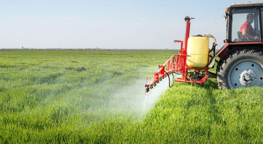 Tracteurs pulvérisant des pesticides dans un champ
