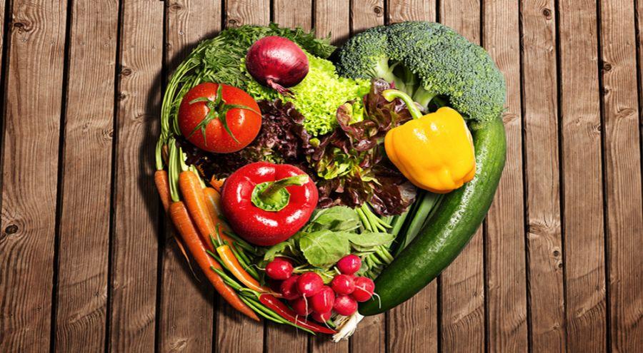 des légumes disposés en cœur sur une table en bois