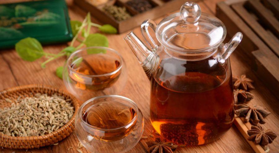 une théière et des tasses de tisane sur une table en bois avec des épices