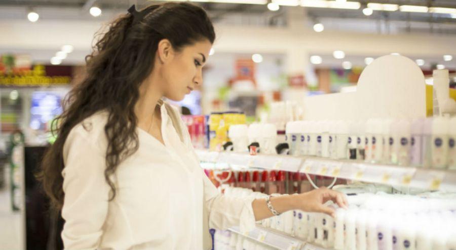 une femme prend des cosmétiques dans un rayon de supermarché