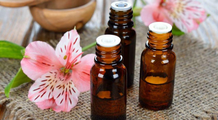 des flacons d'huiles essentielles à côté d'une fleur sur une table