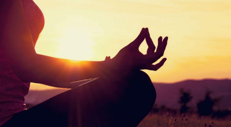 une femme médite devant un coucher de soleil