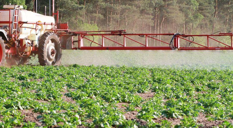 Tracteur pulvérisant son champ de pesticides