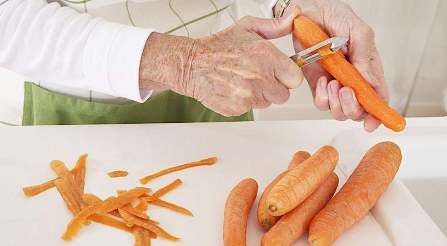 Une personne épluche des carottes vigoureusement dans sa cuisine
