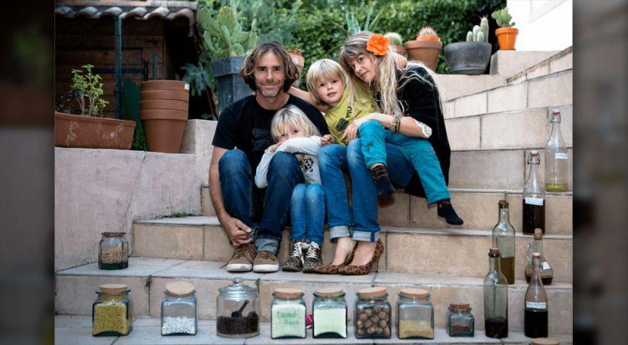 Une famille qui a fait le choix d'un mode de vie sans dechet pose devant ses bocaux de cuisine