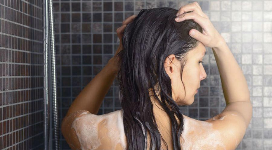 Une femme sous la douche se lave les cheveux