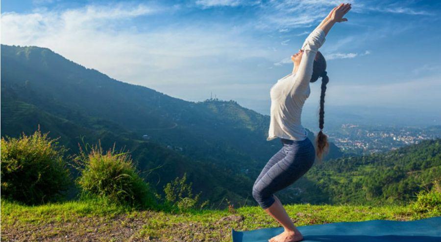 une femme fait du yoga à la montagne
