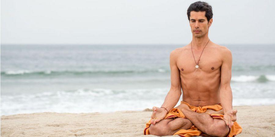 un homme médite en tailleur sur la plage