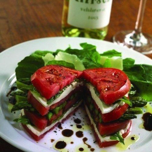 un swandich tomates, mozzarella, asperges et salade dans une assiette blanche