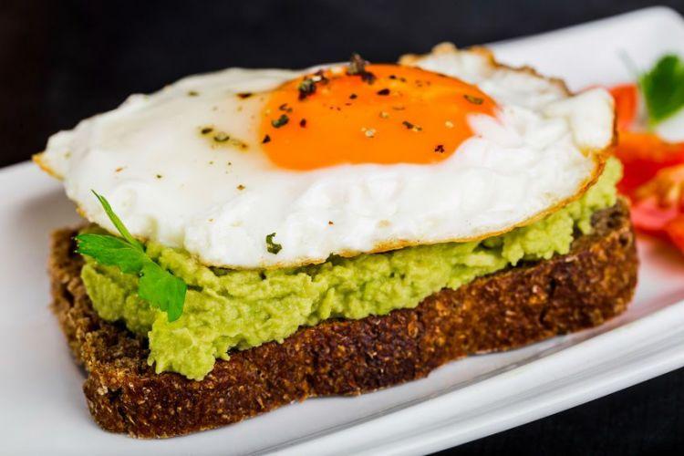 Une tartine de pain avec de l'avocat et un œuf au plat