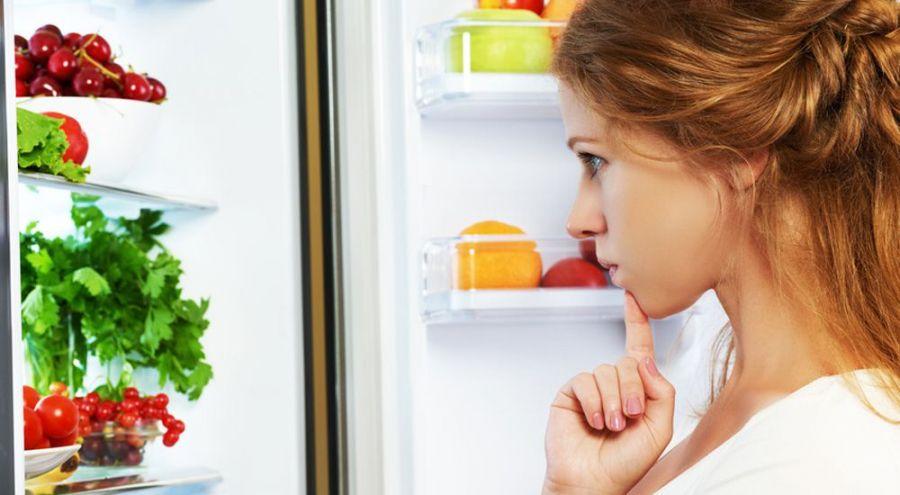 Jeune femme analysant le contenu dans son frigo