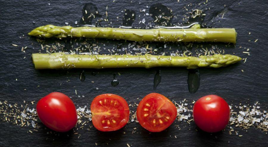 des asperges au dessus de tomates sur une ardoise