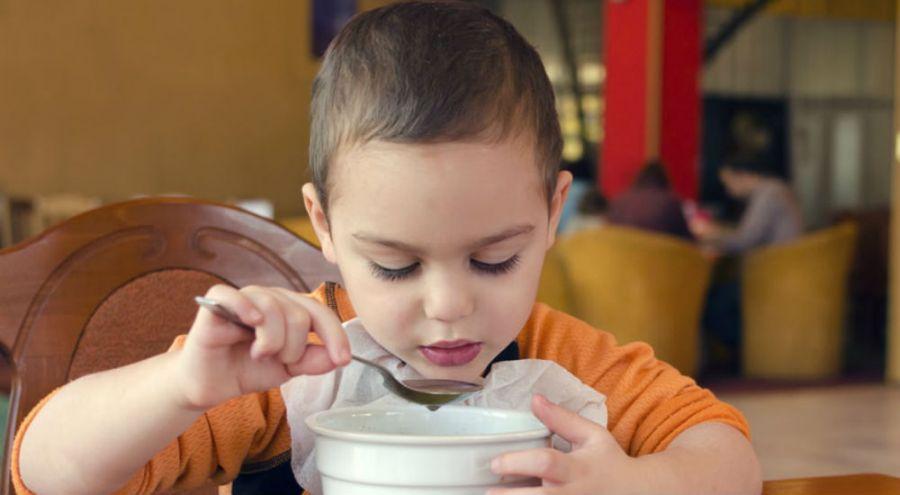 Un enfant mange une soupe dans un bol avec une cuillère dans une cantine
