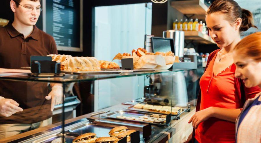 une mère et sa fille regardant les produits d'un boulanger