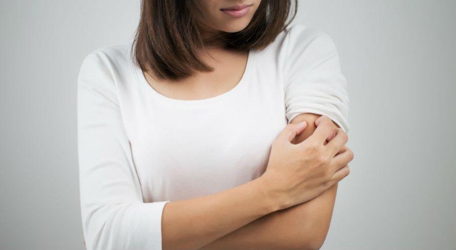 une femme se grattant le bras