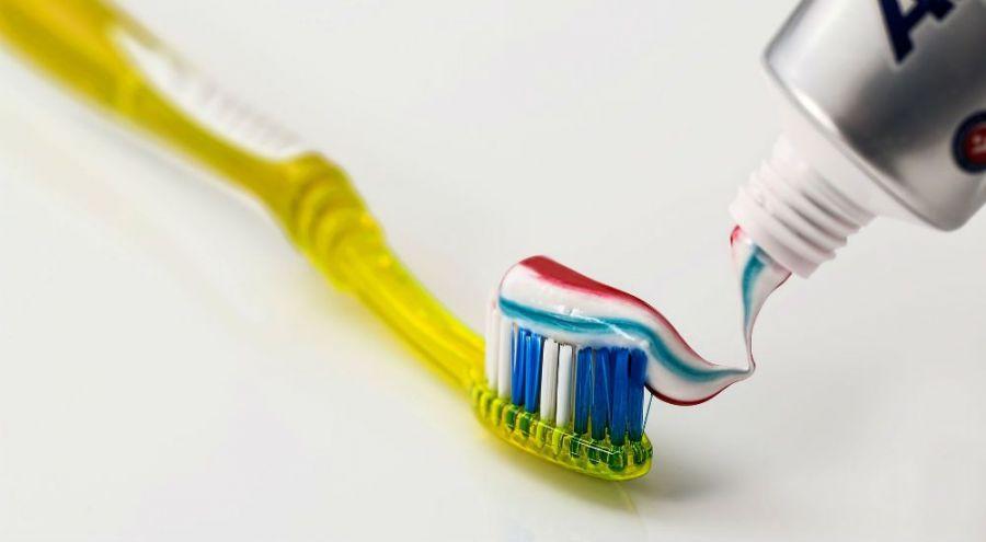 une brosse à dent jaune avec du dentifrice dessus