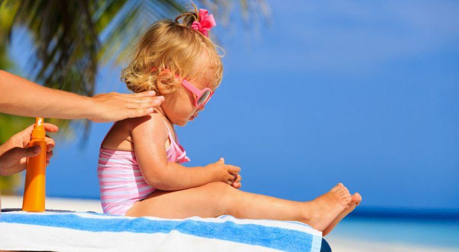 une maman met de la crème solaire à son enfant