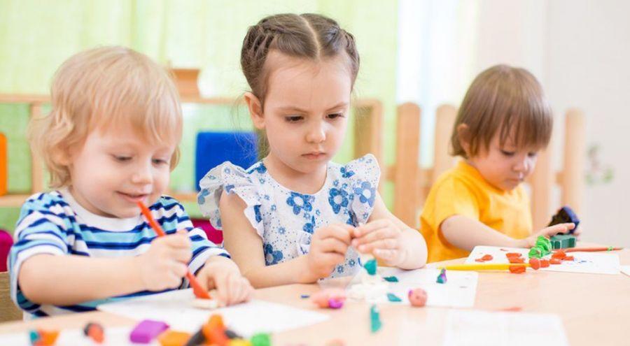 trois enfants en train de jouer avec de la pâte à modeler sur une table