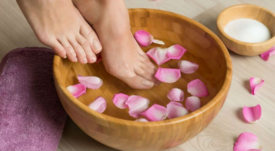 des pieds de femme qui trempent dans de l'eau contenant des pétales de roses