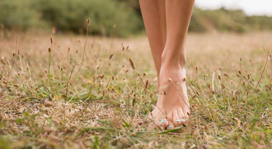 une femme marche pieds nus dans l'herbe