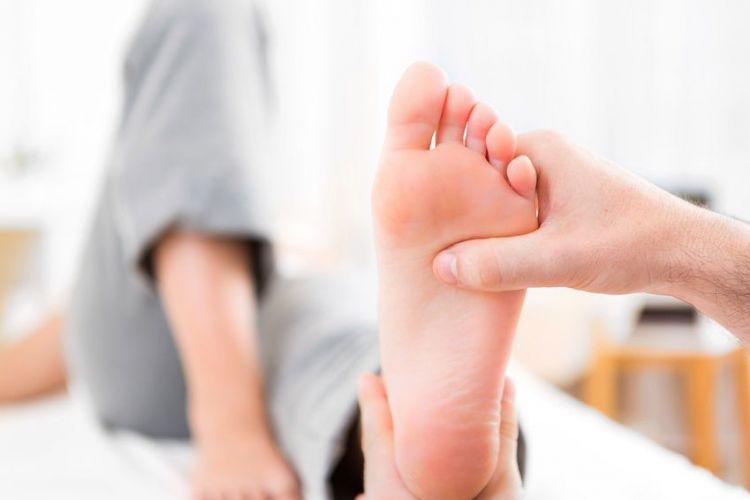 une femme se fait masser les pieds par un homme