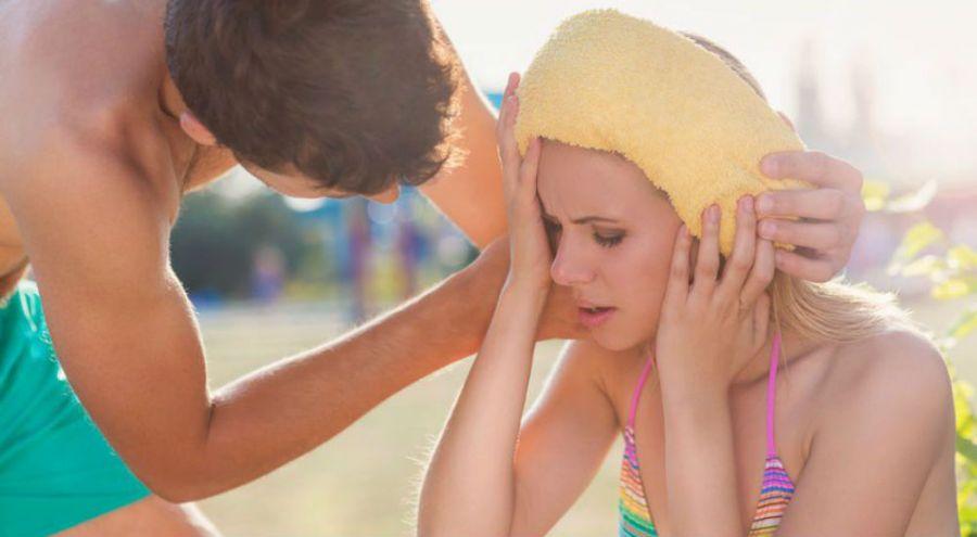une femme ferme les yeux et a une serviette jaune sur la tête. Un homme se penche vers elle