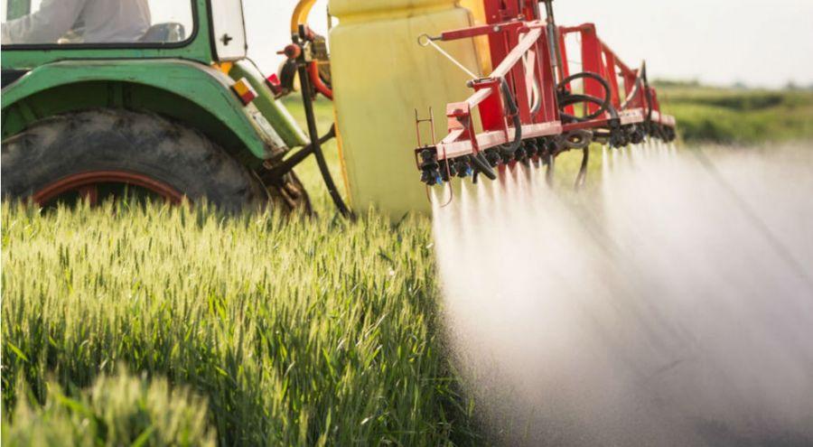 épandage de pesticides dans un champs avec un tracteur