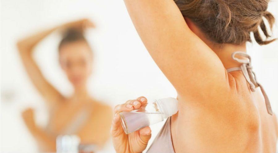 une femme se met du déodorant avec des sels d'aluminium