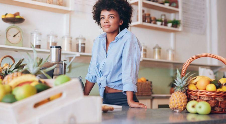 Femme souriant dans sa cuisine entourée de bocaux