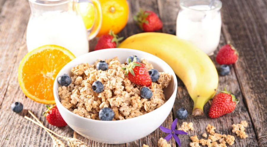 un petit déjeuner avec un bol de muesli et des fruits