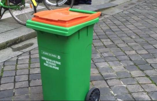 une poubelle orange dans les rues de Paris