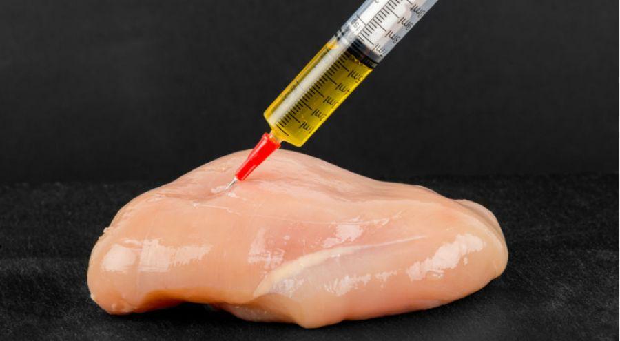 une viande piquée avec une seringue d'antibiotiques