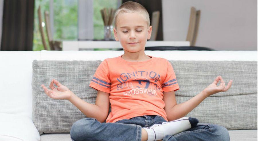 un enfant qui médite en tailleur sur son canapé
