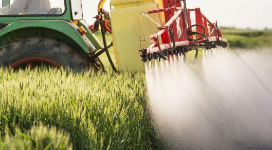 un tracteur déverse des pesticides sur une zone agricole
