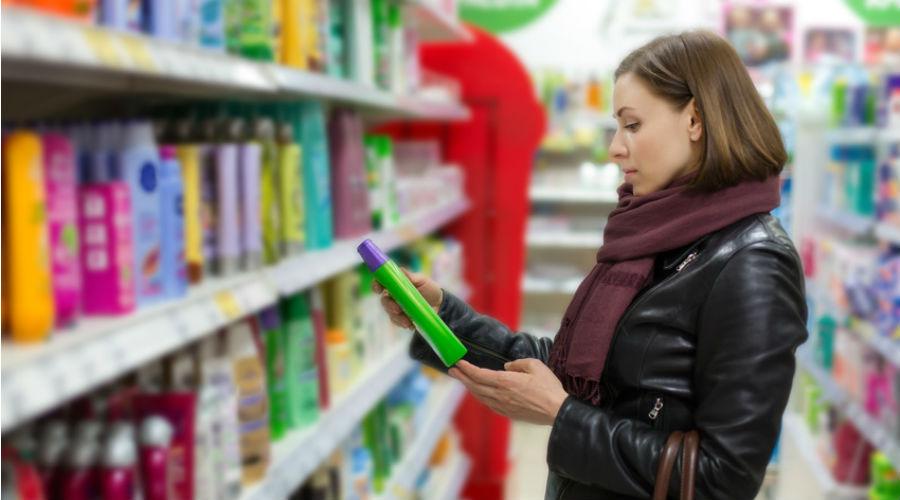 femme qui choisit un shampoing dans un supermarché