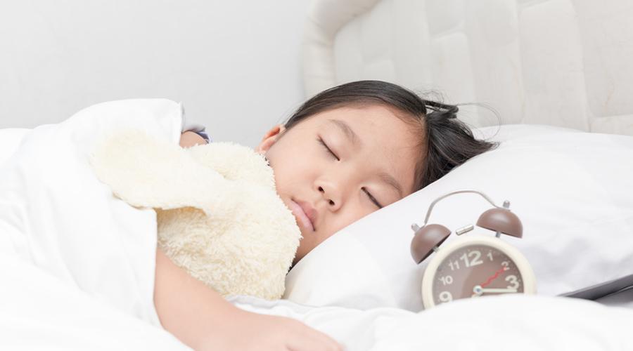 Une petite fille dort sur un lit