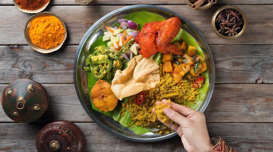 Une personne mange avec les doigts un plat indien