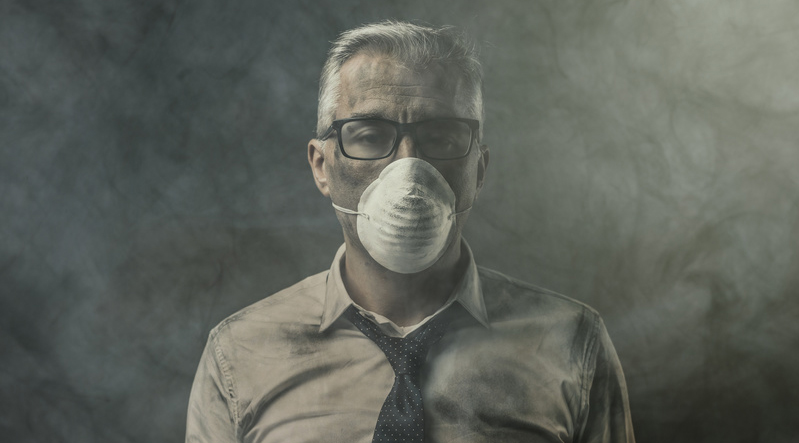 Un homme avec un masque dans une atmosphere polluée