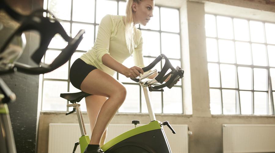 Femme sur ujn vélo à la salle de sport